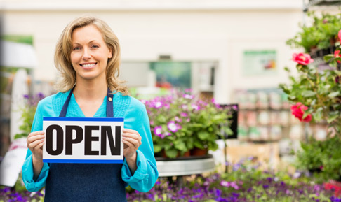 A female flower shop business owner holding a sign that says open